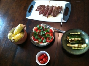 A summer meal from the grill; flank steak, corn, zucchini, cherry tomatoes, fresh mozzerella, roasted pepper, and basil salad